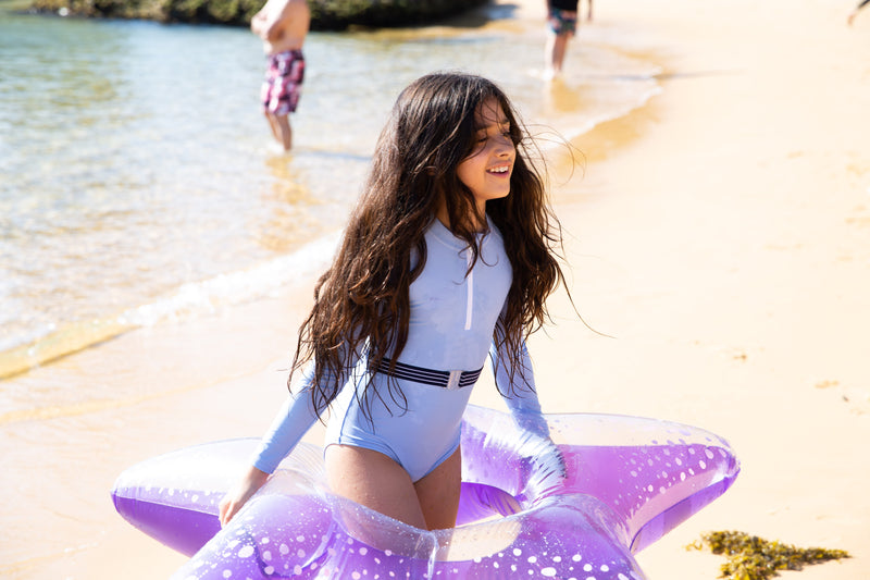 A girl on the beach wearing the Blue Lagoon One Piece Suit with belt