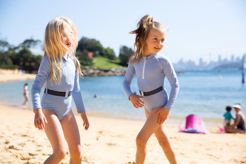 Two girls on beach wearing the Blue Lagoon One Piece Suit with belt