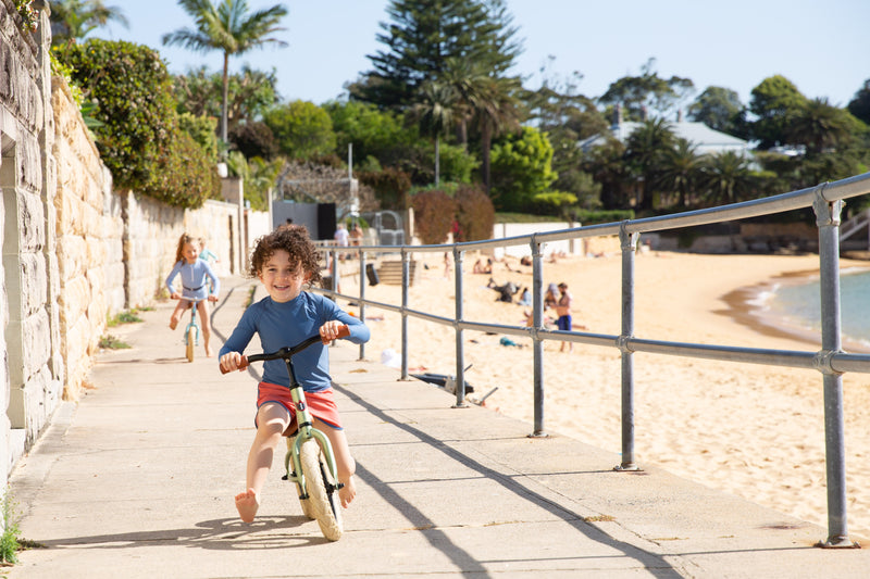 Boy On Bike Wearing Ocean Blue Rash Guard With Long Sleeves