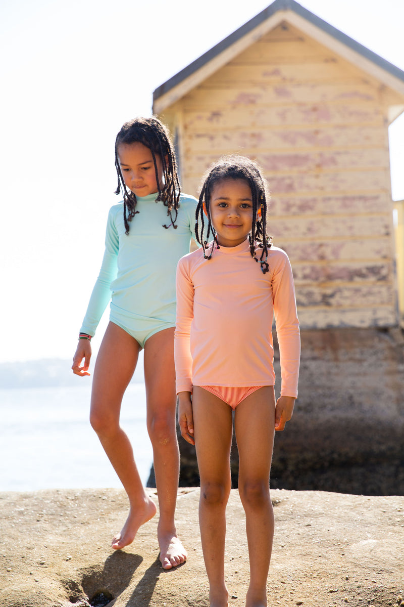 Two Girls Standing On Rock Wearing Rose Peachie And Green Rash Guard And Swim Brief