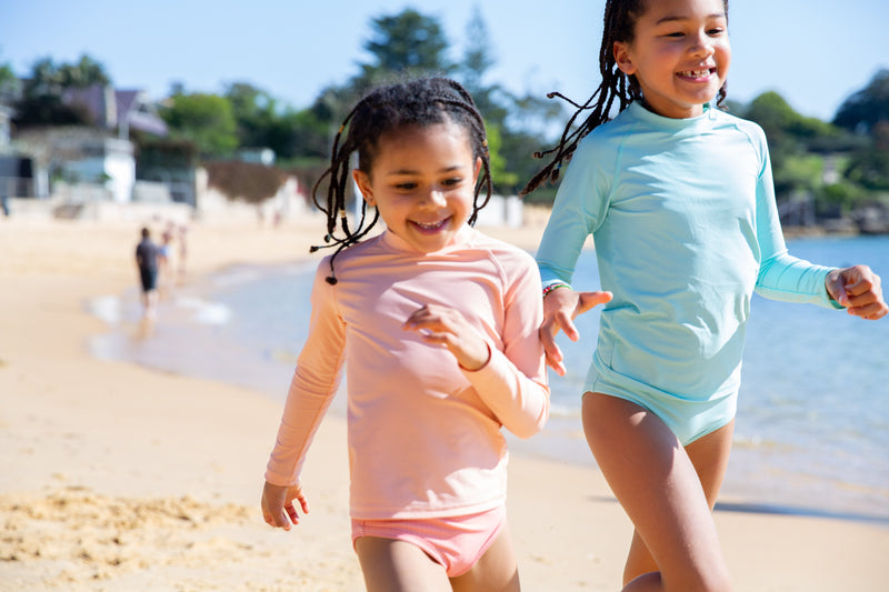 Girls Running On A Beach Wearing Peach And Green Colour Rash Guards With Long Sleeves