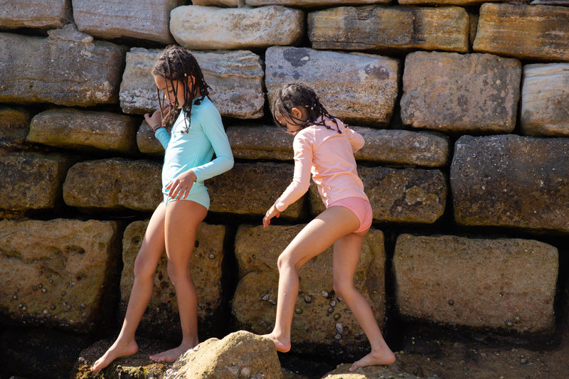 Two Girls Climbing Over Rocks Wearing Rose Peachie And Green Rash Guard And Swim Brief