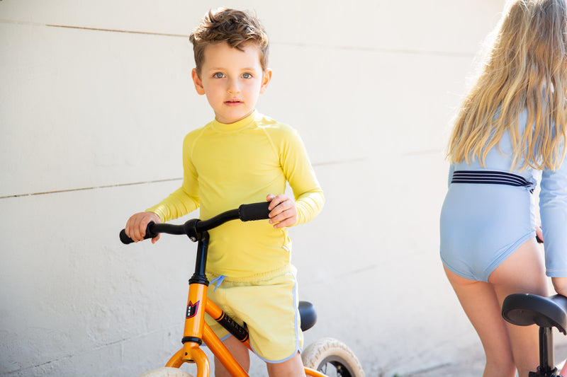 Boy On Bike Wearing Yellow Citrus Rash Guard With Long Sleeves