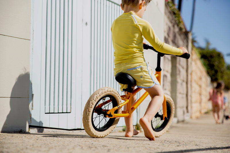 Back Of Boy On A Bike Wearing Yellow Citrus Rash Guard With Long Sleeves