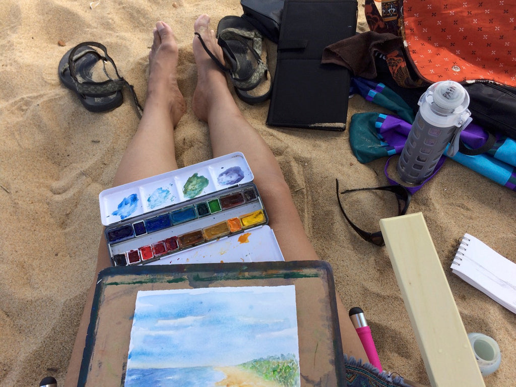 sitting on beach with painting on lap