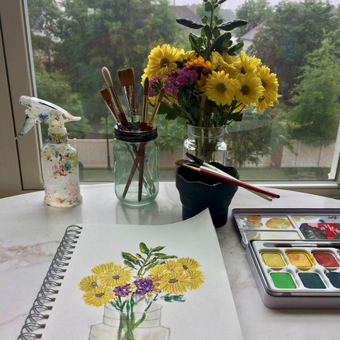 Flowers, paints, and sketchbook on a desk in front of a window.