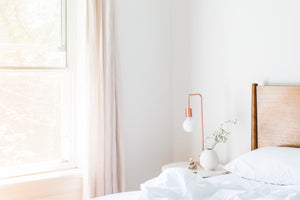 soft lighting in a white light filled room a bed with a lamp on a table by a window