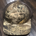 Our camo trucker hat with tan embroidery.