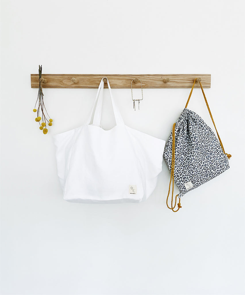 Essential Tote - White. Our Essential Tote is the perfect everyday carry-all bag made from 100% linen with a large interior pocket 35 x 27cm, designed to fit your laptop. Inside, the bag is fitted with a printed Belgian linen detail with antique brass D ring to secure your keys. Perfect for a day at the beach, to take to the office or farmers markets.