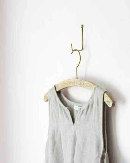 Wood and Brass Shirt Hanger. Hand-carved mango wood with brass hook. These will accommodate lighter items like shirts and dresses. Shop-keepers note: these are a great alternative to traditional commercial hangers. Light-weight and slim profile. Tones and grain of wood will vary.