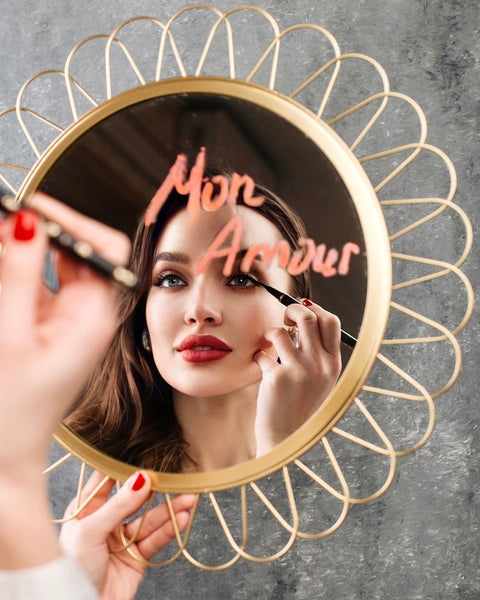 """Woman applying the Feutre Fin eyeliner in a mirror with the words """"Mon Amour"""""""