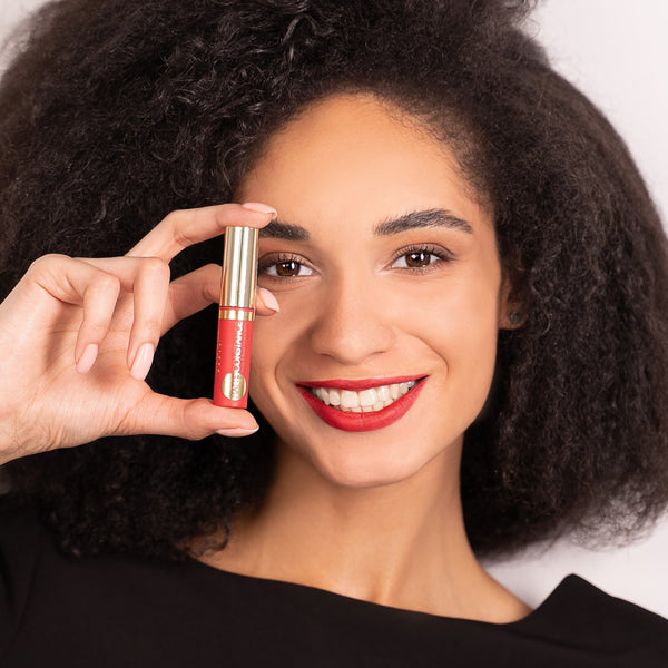 Smiling woman with Vivienne Sabo lipstick in hand