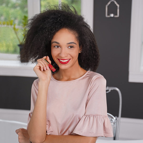 Young woman smiling and holding Matte Constance Lipstick