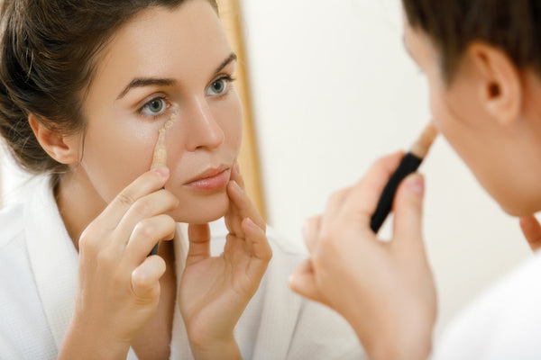 Woman applying makeup under eyes