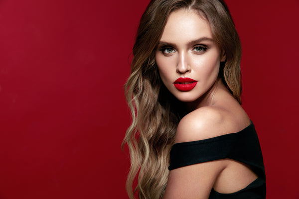 Model with bold red lipstick in front of red backdrop