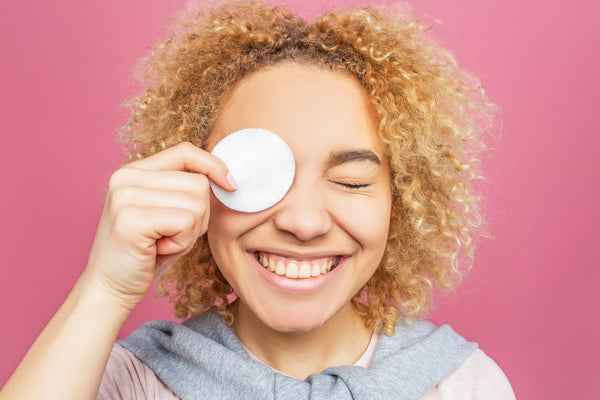 Young smiling woman holding a cotton pad over her eye