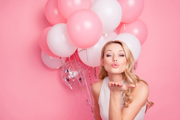 Woman blowing kisses with soft pink lipstick on