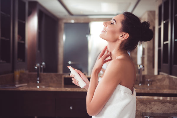 Happy woman applying lotion on neck