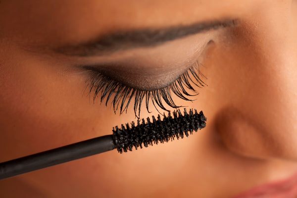 Young lady applying mascara