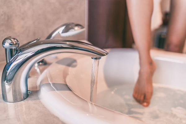 Woman dipping her foot into a bath