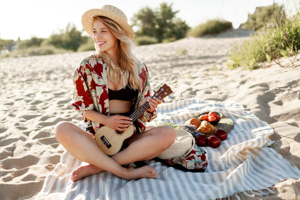 Blonde woman in straw hat sitting on cover on the beach