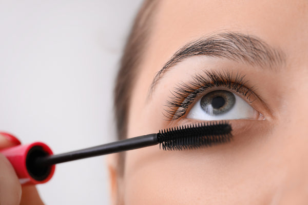 Woman coating one side of lashes with mascara