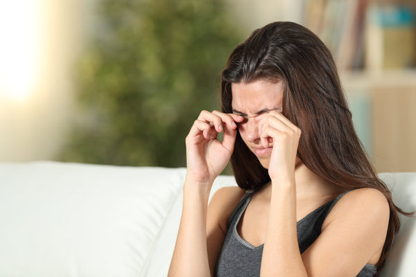 Woman itching her irritated eyes
