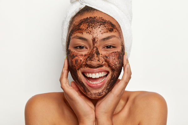 Smiling healthy woman with coffee face mask on