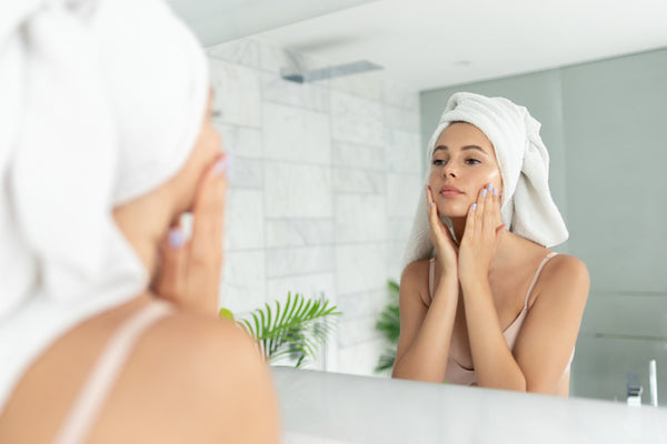 Woman with towel on her head washing face in the morning