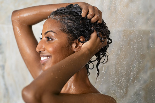 Woman washing hair showering in bathroom at home