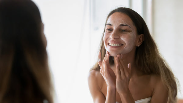 Young happy woman washing face in mirror