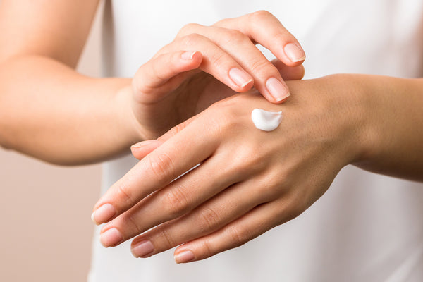 Closeup of woman applying protective cream on hands