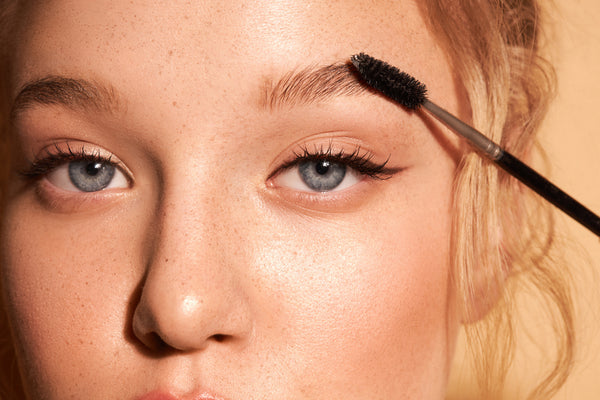 Woman combing eyebrows with a brush closeup