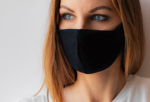 Close-up portrait of a young woman in a black medical mask and white T-shirt