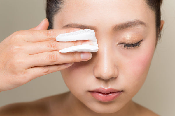 A woman removing her eye makeup with a cotton pad