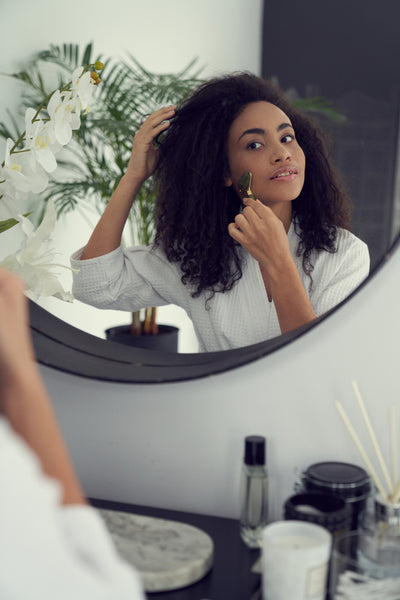Young woman using face roller in mirror