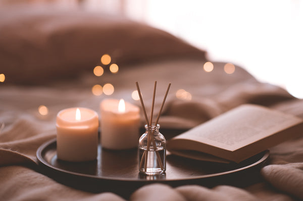 Bamboo sticks in bottle with scented oil next to lit candles