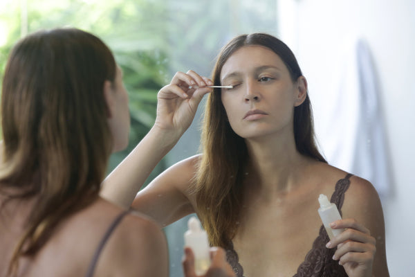 Woman applying serum for eyelash growth in front of the mirror
