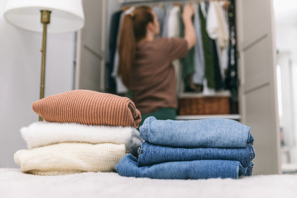 A woman sorting through her closet in front of folded clothes