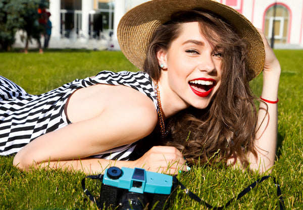 Girl laying on the grass in a sun hat