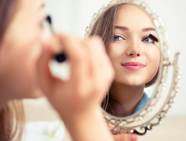 Young lady applying makeup in a small mirror