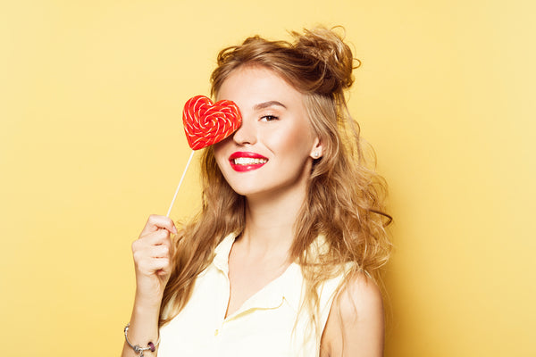 Pretty girl with lipstick and mascara on, holding lollypop over eye