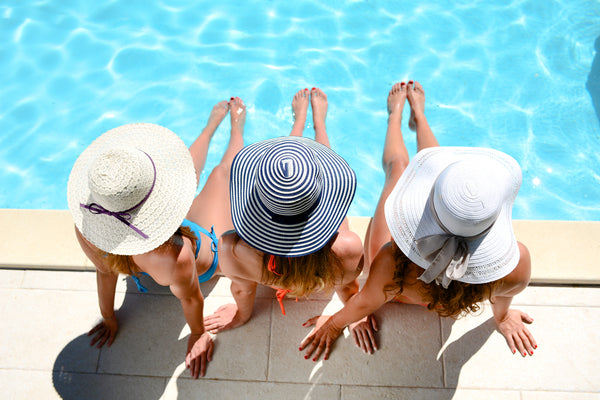 Three beautiful young women with sun hats, sitting by the poolside