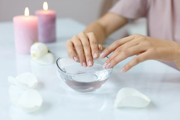 Closeup of woman's hands soaking in bowl of water