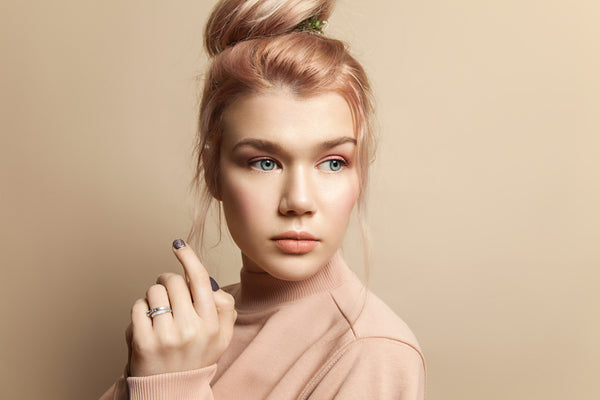 Portrait of a beautiful young woman in soft powdery beige pastel colors with natural make-up