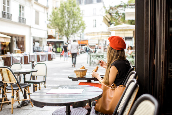Woman in beret sitting at outdoor café