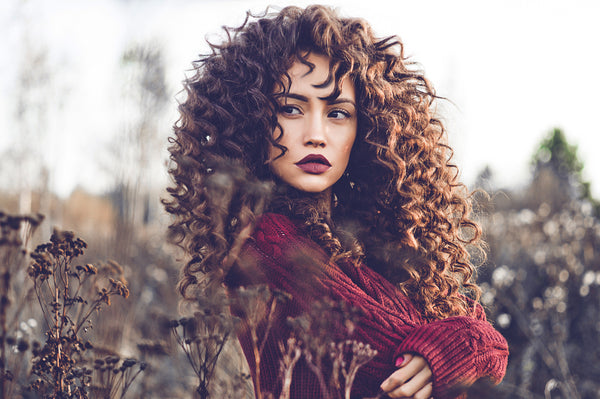 Woman outdoors with burgundy lipstick and full hair