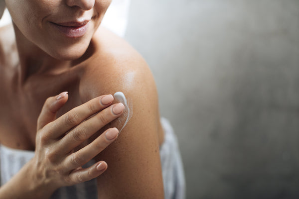 Smiling woman wrapped in a towel and applying moisturizer