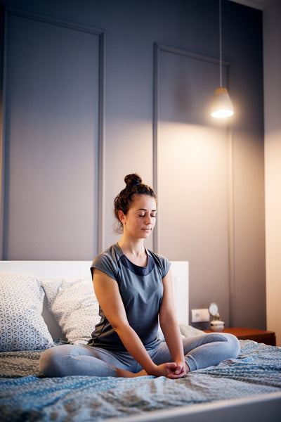 Healthy woman meditating on bed