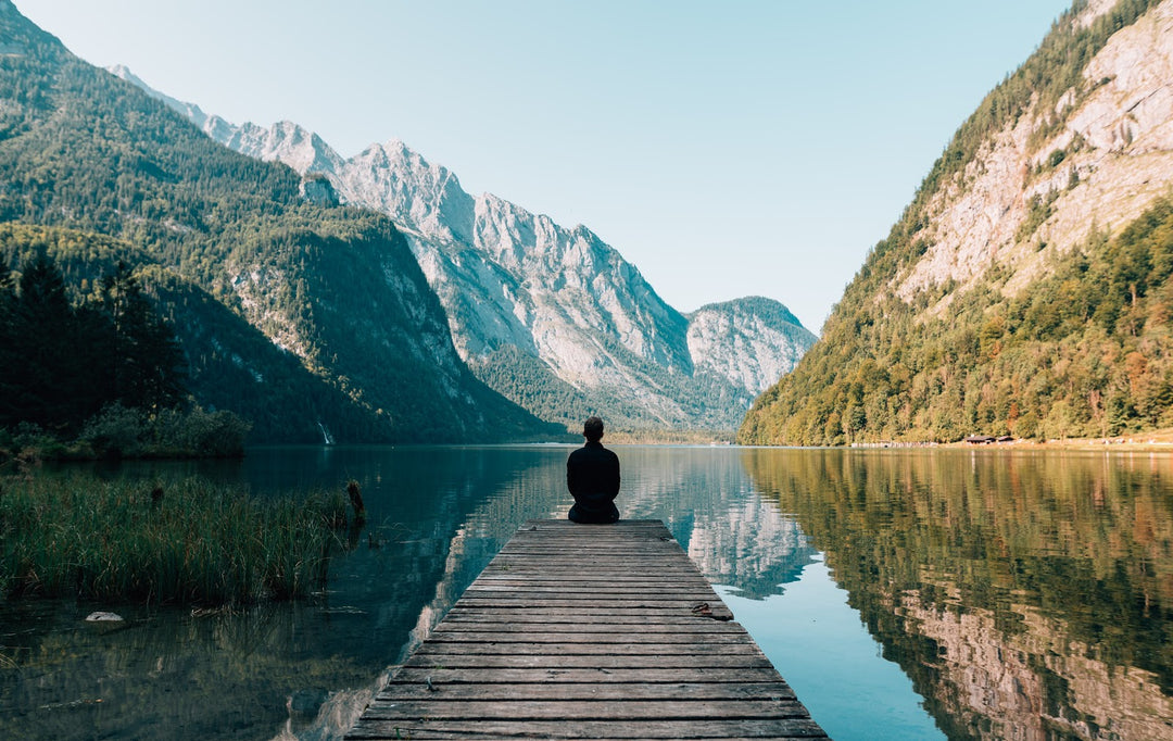 Person looking across peaceful, scenic lake surrounded by mountains